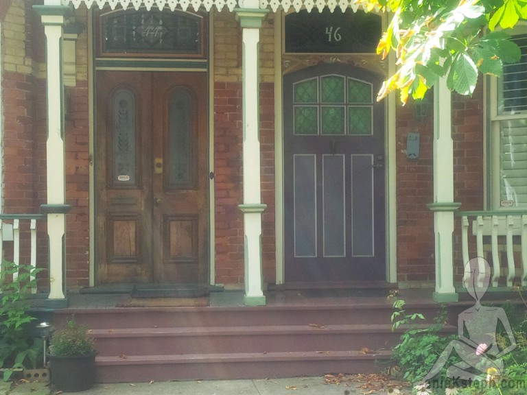 Toronto Doors view from the sidewalk. A purple door with mauve wainscotting aside a brown bi-fold door with dark wood stain.