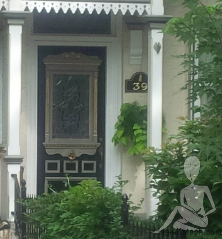 A black and gold door with a large glass lite insert on a street in downtown Toronto Canada. The homes have only street parking, but large front yard and large tree-foliage patches.
