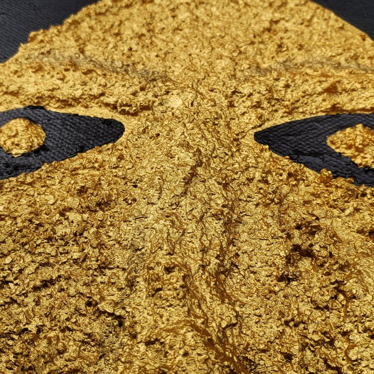 A human face painted in gold with textured and raised sculpture relief on the canvas with a black painted background.